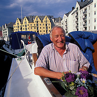 Europe, Norway. (MR) Johnny Dale eats breakfast on sailboat in Ålesund on sunny morning.