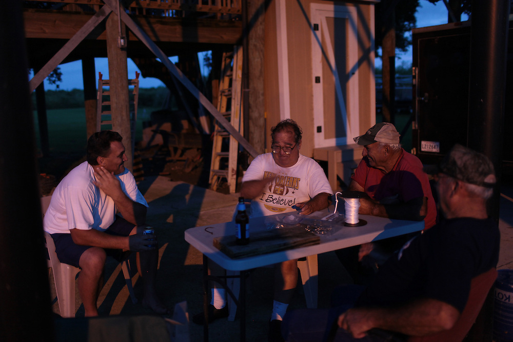 Local fishermen gather together at dusk to drink beer in Delacroix, LA on August 30, 2010.