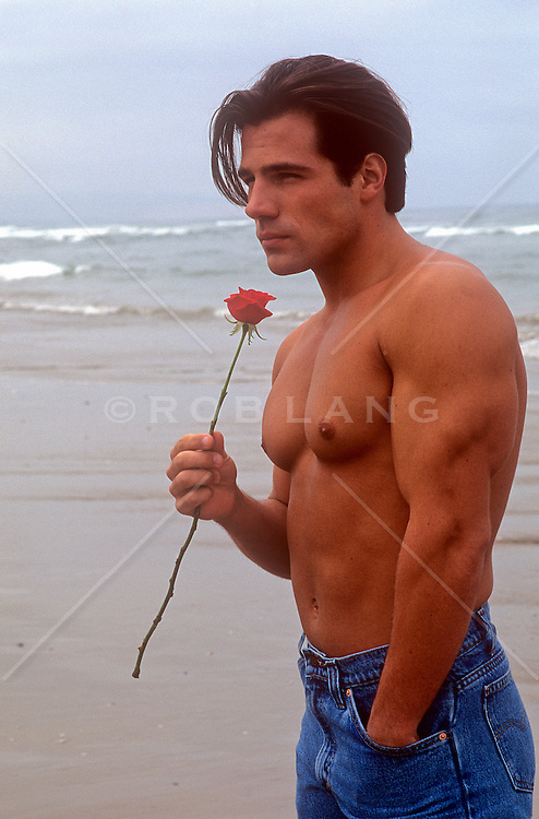 sexy shirtless man on the beach holding a red rose