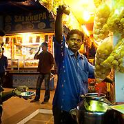 A vendor at a food stall on Juhu Chowpati beach serving dripping Pani Puri. Mumbai, August 2009