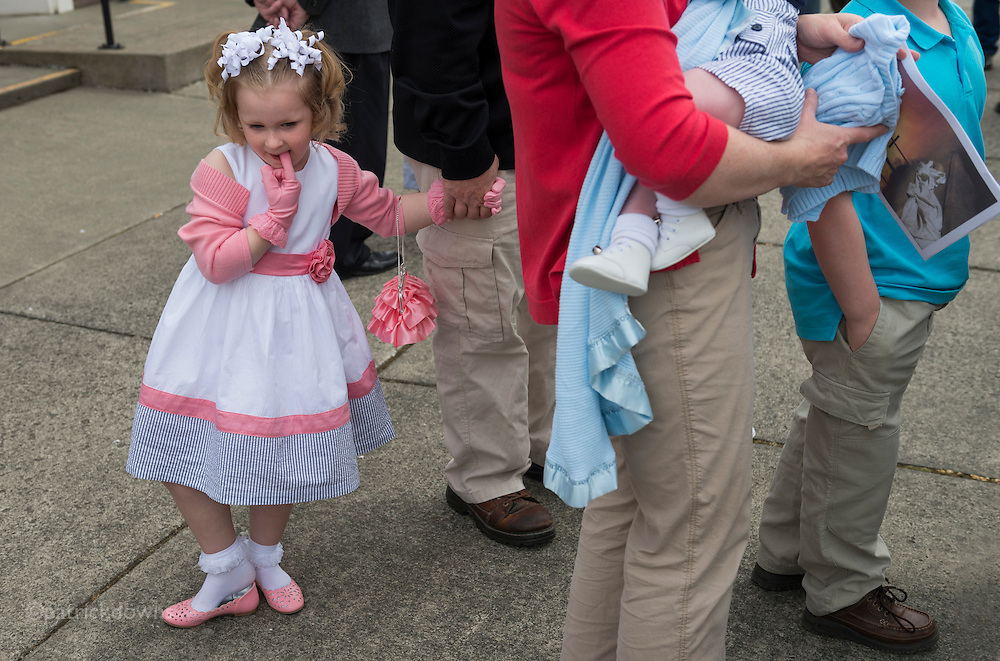 A girl in her Sunday dress outside church after mass.