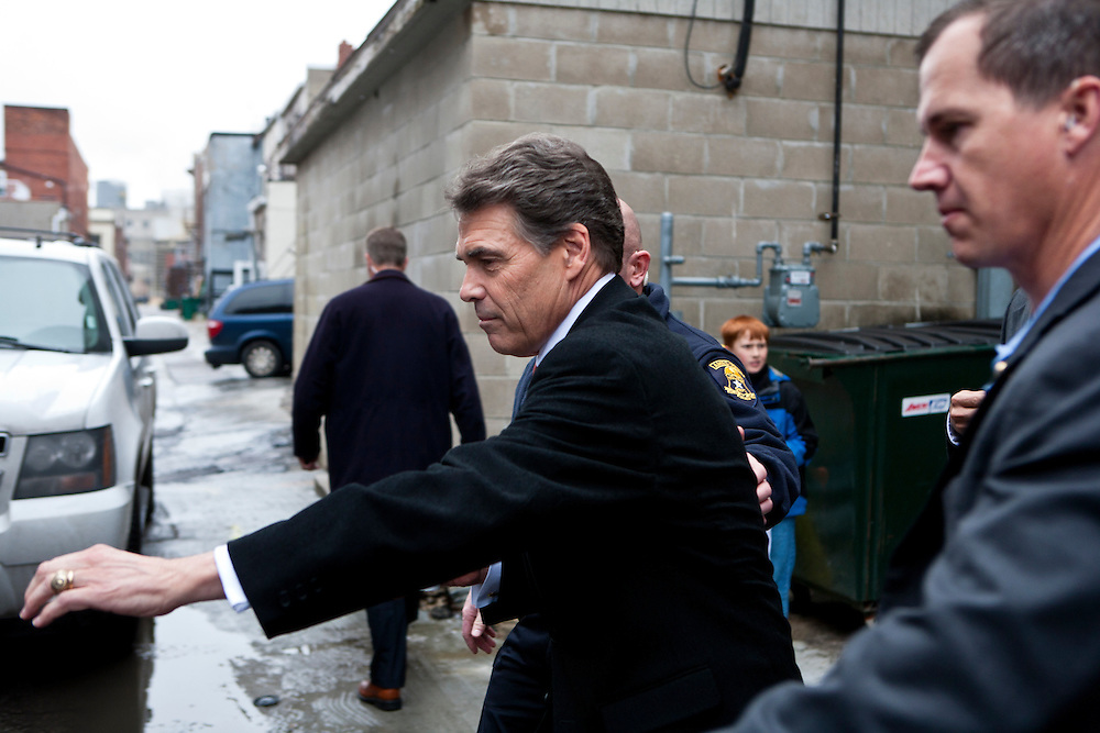 Republican presidential candidate Rick Perry reaches for the door of his SUV after speaking at a campaign meet and greet on Sunday, December 11, 2011 in Ames, IA.