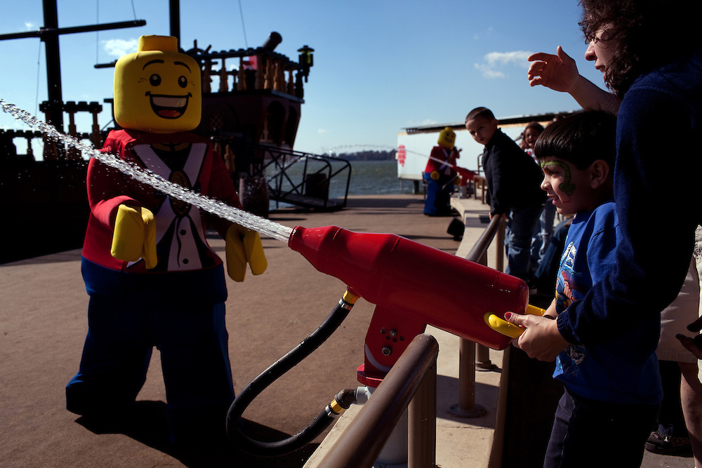 Ncolas Fagundo, 5, with his mother Yolanda Fagundo from Boston, fires a watergun at a lego character during the Priates' Cove Live Water Ski Show in Legoland in Whitehaven, Florida on February 11, 2012.