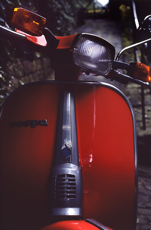 Close-up of the front fender of a shiny red Vespa in Germany. Main headlight, blinker lights and rear view mirror on the handlebars.  Red painted fender with chrome accents running down center of fender and framing the outside of it.