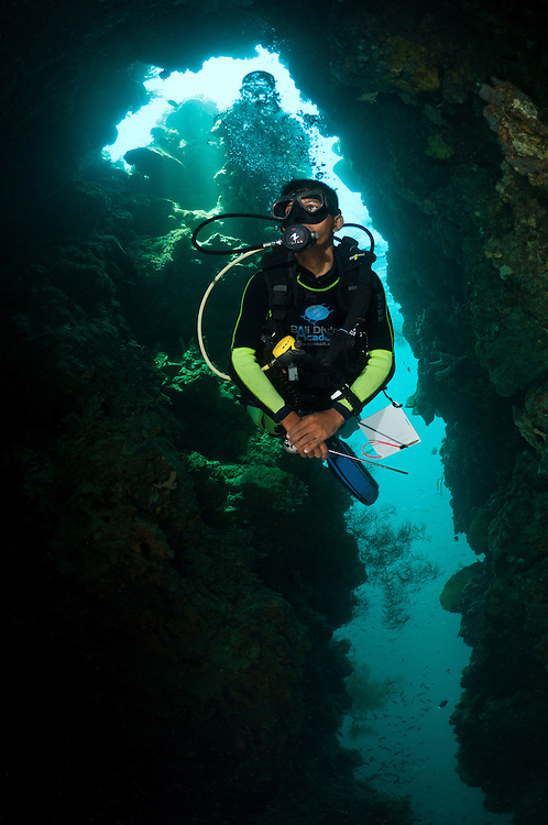 Diver exploring a narrow cavern, Menjangan, Bali, Indonesia. Menjangan is protected from the strong currents that sweep between Java and Bali and as a result has clear, warm waters and good reefs - the walls and shallow coral gardens of the island are some of the best in Bali.