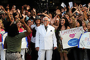 This handout photo from KFC shows Colonel Bob Thompson, center, a Col. Sanders look-alike and spokesperson for KFC from Lawrenceburg, Ky., as he greets the camera at the opening of the second American Idol auditions Monday, July 21, 2008 in front of the Kentucky Fair and Exposition Center in Louisville, Ky. Col. Bob, in the crowd to promote KFC by asking Idol hopefuls to do a chicken dance, was asked by the producer to introduce the Louisville audition. (Photo by Brian Bohannon)
