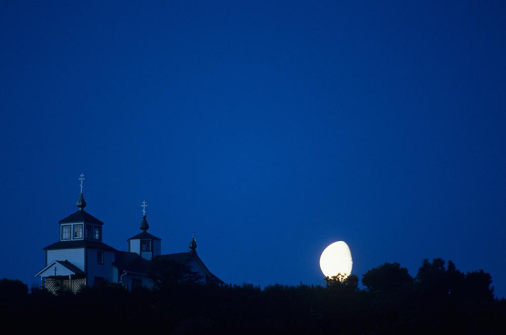 USA, Alaska, Ninilchik, Moonrise behind Russian Orthodox Church on bluff above Cook Inlet on Kenai Peninsula