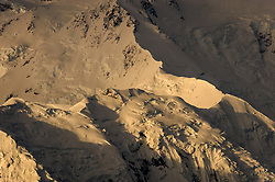 "Denali (Athabaskan for ""The High One"") basks in morning light at sunrise in Denali National Park and Preserve in Alaska. The snow and glacier covered mountain, part of the Alaska Range soars to a height of 20,310 feet. Denali is the tallest mountain on the North American continent. Although Mt. Everest is higher, the vertical rise of Denali is greater. This view is a small detail from the north slopes of the mountain seen from Wonder Lake."