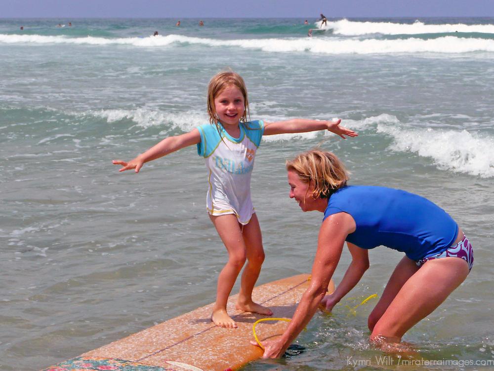 USA, California, La Jolla.  Mother teaches daughter to surf at La Jolla Shores.