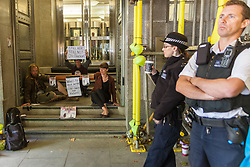 London, August 18th 2014. Two activists from anti-fracking group No Dash For Gas, their arms linked in a protective tube and their hands superguled to the steps, blockade the entrance to the Department of Environment, Food and Rural Affairs, in protest against redacted information in a government report on the potential impacts of shale gas exploration on rural communities.