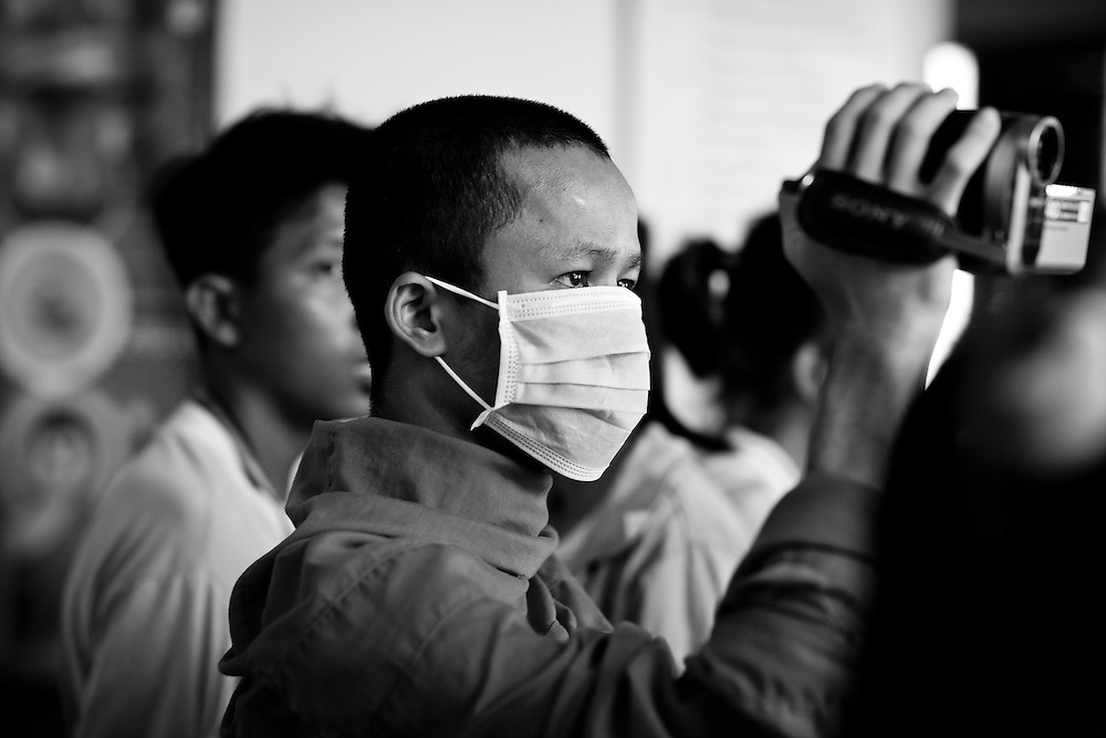 A buddhist monk records video of his fellow monks as they pray over the coffin of of a female victim of the stampede tragedy in Phnom Penh, Cambodia on November 22nd, 2010.