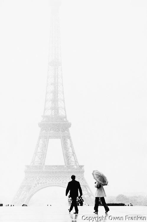Paris, France --- Man and Woman Walking near Eiffel Tower --- Image by © Owen Franken/CORBIS