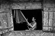 A man repairs a fishing net near Luang Prabang, Laos.