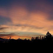 Rays of sun set glow orange over the Olympic Mountains and Puget Sound, Seattle, Washington, USA.