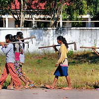 Young Girls Going to Work in Farm Fields in Cheung Prey District, Cambodia<br /> The Cheung Prey District is a remote region of Cambodia made famous for selling fried spiders in Skuron, its capital city.  The people are hardworking farmers yet very poor.  Typically, their rickety houses are on stilts and pieced together by scrap metal, old wood and tree limbs.  Most farmers cultivate their land by hand.  The lucky ones use oxen.  These young girls crawled out of the back of a crowded truck after school.  They immediately picked up hoes and walked towards the muddy fields to help their parents.