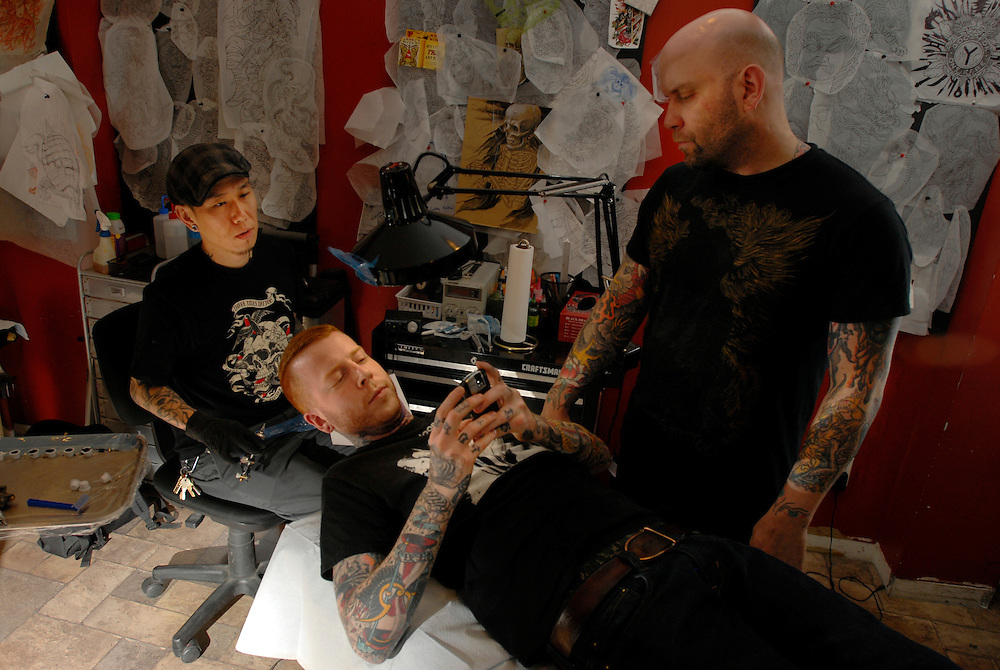 Tattoo artists at Invisible in New York City pause for an important BlackBerry moment.