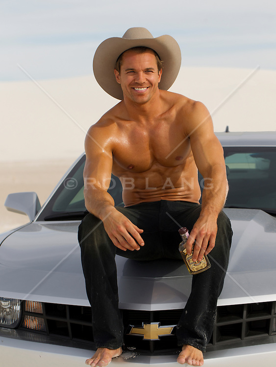 shirtless man in a cowboy hat sitting on the hood of a car in the desert holding a bottle of alcohol