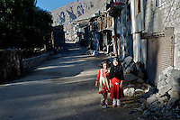 Two sisters pose for a portrait on a quiet street, Kargil