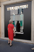 Frumpy elderly lady looking to upgrade her fashion at Valentino, Rome, Italy