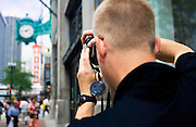 Tourist takes a photo of the Chicago Theater in downtown Chicago.