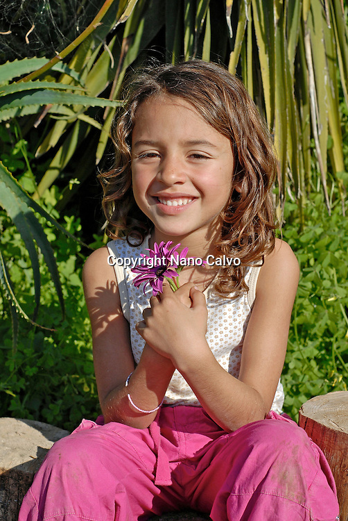 Cute brazilian six year old girl holding a flower in nature