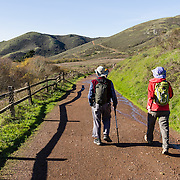Hikers enjoy a sunny stroll through coastal foothills along Tennessee Valley Trail, Golden Gate National Recreation Area/Marin Headlands, Marin County, California, USA.