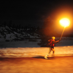 A man runs down a dirt road with a torch during a winter full moon party in the mountains of western New Mexico.