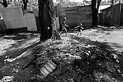 Angie chases her baby brother Jose in a game of catch with her brothers. This clearing from all the shacks can be a dangerous place; many addicts can be seen smoking crack here amongst the burnt garbage.