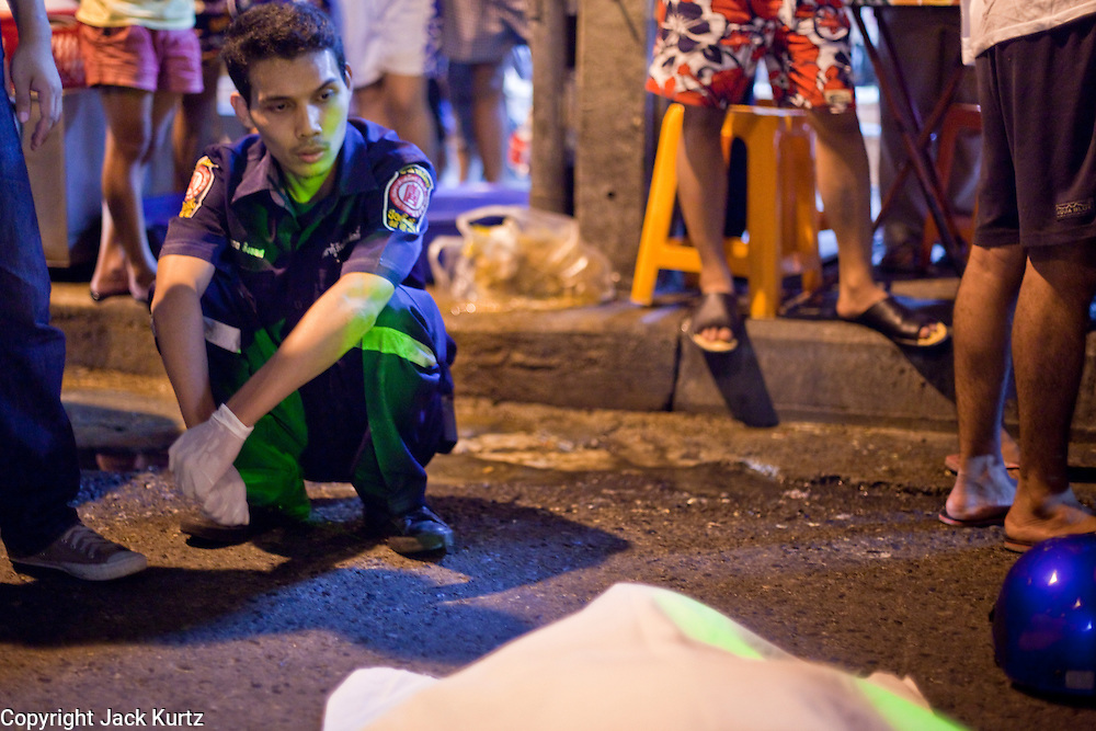 "Oct. 2, 2009 -- BANGKOK, THAILAND:  A volunteer from the Poh Teck Tung Foundation sits on the side of a Bangkok street after trying in vain to save a man's life after a motorcycle accident. The 1,000 plus volunteers of the Poh Teck Tung Foundation are really Bangkok's first responders. Famous because they pick up the dead bodies after murders, traffic accidents, suicides and other unplanned, often violent deaths, they really do much more. Their medics respond to medical emergencies, from minor bumps and scrapes to major trauma. Their technicians respond to building collapses and traffic accidents with heavy equipment and the ""Jaws of Life"" and their divers respond to accidents in the rivers and khlongs of Bangkok. The organization was founded by Chinese immigrants in Bangkok in 1909. Their efforts include a hospital, college tuition for the poor and tsunami relief.    Photo by Jack Kurtz / ZUMA Press"