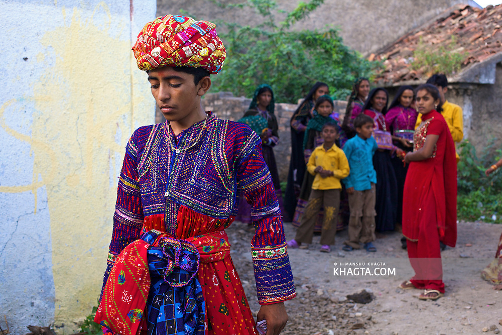 A shy young bridegroom standing while people of the village gazing at him from a distance in a village near Bhuj, Gujarat, India