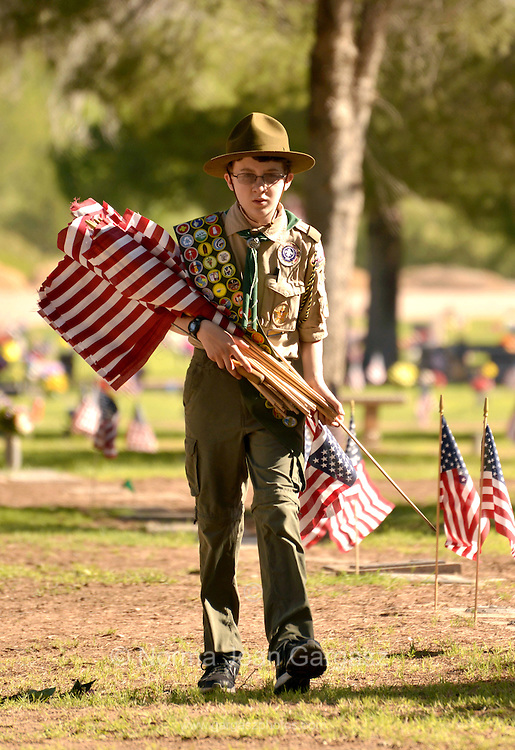 "Boy Scout, Ray Langlais, 13, places flags on May 25, 2013 at the graves of deceased U.S. military veterans in preparation for Monday's Memorial Day services in Tucson, Arizona, USA.  Langlais says that he helps place the flags to ""help my country""."