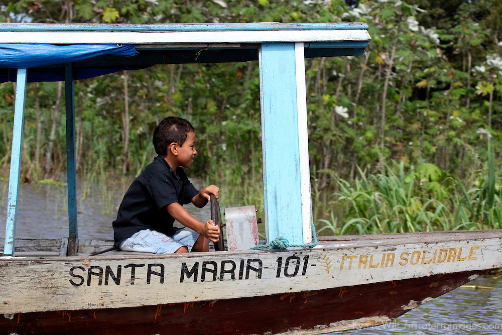 South America, Brazil, Amazon. A young boy gleefully captains a boat on the Amazon River.