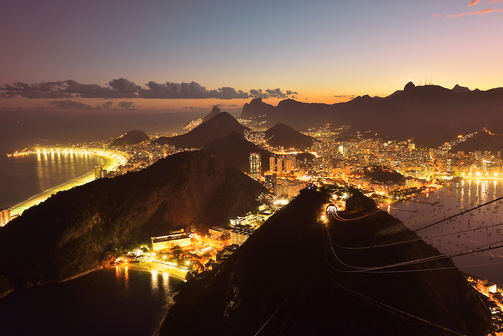 View at dusk from Sugar Loaf Mountain over the city of Rio, with Corcovado and Christo in the distance, Rio de Janeiro, Brazil, South America