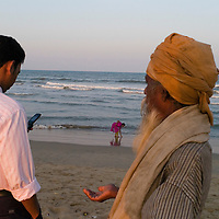 Beggar asking for money which a man uses his mobile phone. Santhome Beach and adjoining Marina Beach in Chennai, India were hit hard by the 2004 Tsunami. Fishermen and their families were the main victims living in their lightweight huts on the long and flat beaches of the area. All structures within 300 metres of the sea have now been banned and any left standing after the Tsunami were demolished. The fishermen and their families have now been relocated to government blocks of flats which has become a Santhome slum for fishermen and their families.