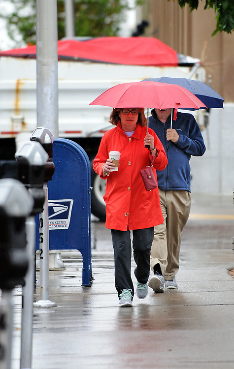 jt042517i/a sec/jim thompson/  M.J Mulcahey of Philadelphia, PA. takes a walk and has a coffee in some of the liquid sunshine that hit the Albuquerque area today .Tuesday April 25, 2017. (Jim Thompson/Albuquerque Journal)