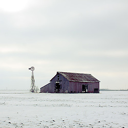 An old dilapidated barn stands against a cold winter landscape on the outskirts of Galesburg, IL.