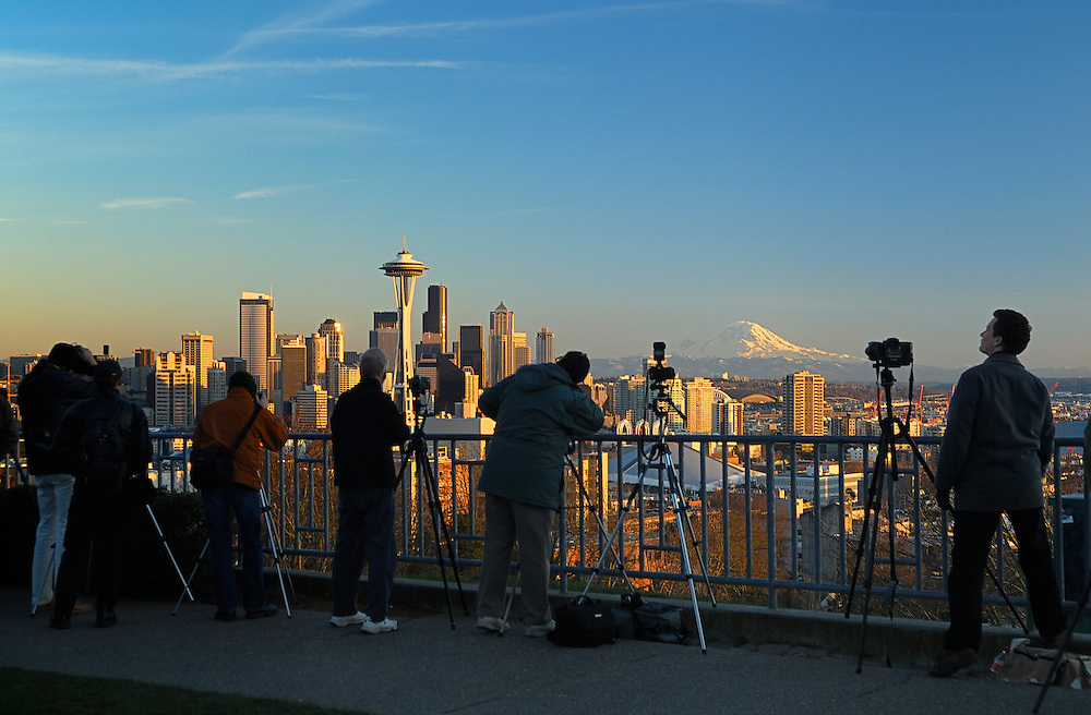 Photographers at Kerry Park on Queen Anne Hill taking photos of the city skyline at sunset with the Space Needle, downtown and Mount Rainier; Seattle, Washington.