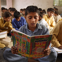 Mohammad Salim, 6, the nephew of one of Mukhtar Mai's accused rapists, studies at the boys school she created after the incident, Meerwala, Pakistan, April 28, 2005. Mai, 33, went against the Pakistani tradition of committing suicide when she brought charges against the men who gang raped her nearly three years ago. With money from the ruling she opened two schools, one for girls, the other for boys, citing that education is the only thing that will stop such acts from happening.