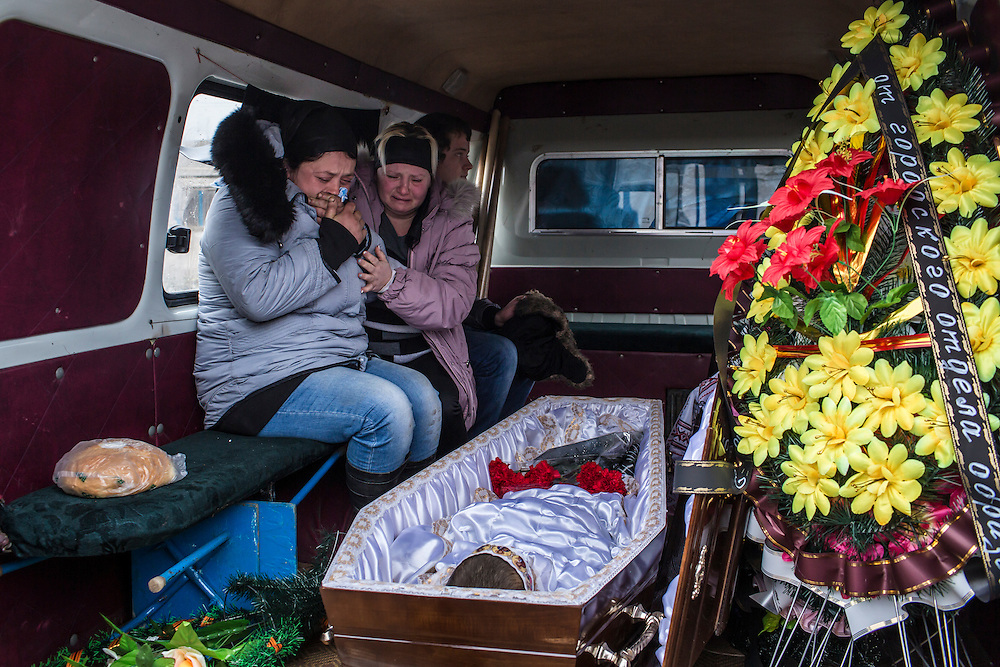 ARTEMIVSK, UKRAINE - FEBRUARY 15: Zhanna Molodetskykh (L) cries over the casket of her son Igor Molodetskykh, 7, who was killed two days prior when a shell hit his school on February 15, 2015 in Artemivsk, Ukraine. A ceasefire scheduled to go into effect at midnight was reportedly observed along most of the front, save for near the embattled town of Debaltseve. (Photo by Brendan Hoffman/Getty Images) *** Local Caption *** Zhanna Molodetskykh