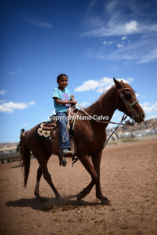 Cute young native american girl riding her horse during Navajo Nation Fair, a world-renowned event that showcases Navajo Agriculture, Fine Arts and Crafts, with the promotion and preservation of the Navajo heritage by providing cultural entertainment. Window Rock, Arizona.