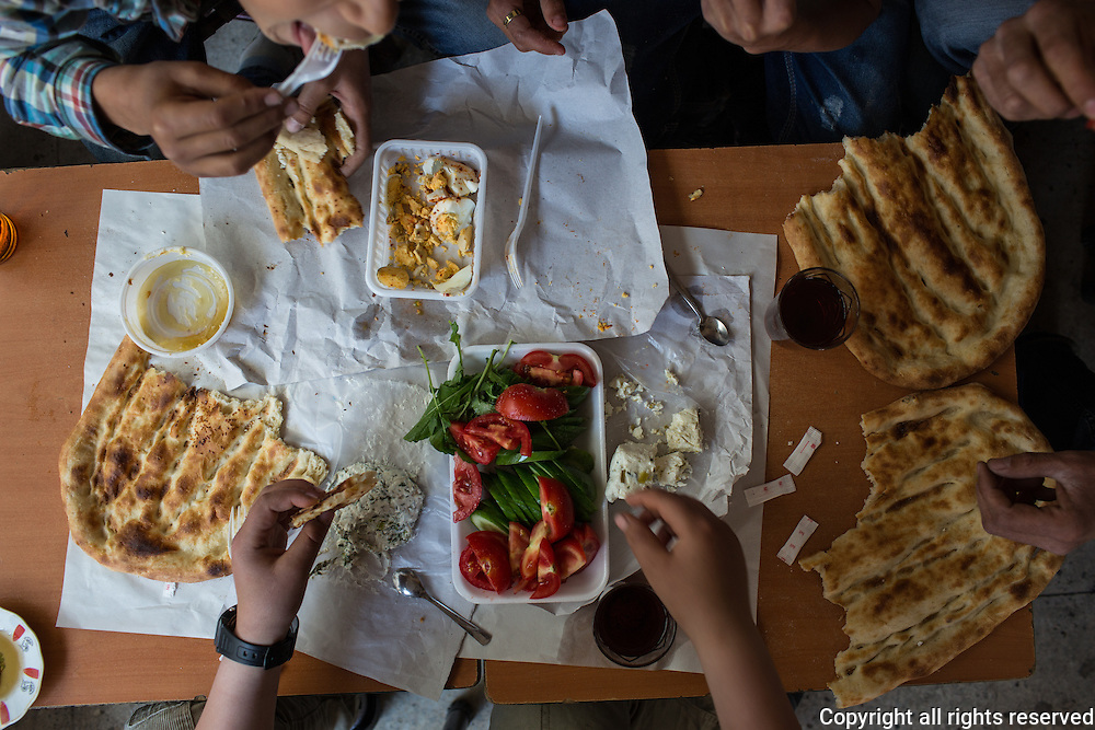A group of boys (8-12 years old) sit down to breakfast in Van. They have purchased the components of their breakfast from a nearby kahvalti salon (like a deli that specialises in breakfast). Their breakfast include honey with kaymak, hard boiled eggs tossed with dried red pepper and parsley, otlu peyniri (fresh cheese made with wild herbs - a speciality of Van), tomato, cucumber, fresh mint leaves, yogurt with cucumber and wild herbs, pide bread and of course tea. Van, Turkey