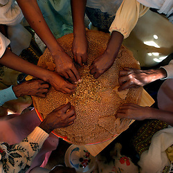 "Tiblits shares the local delicacy called ""Injero"" with her neighbors after Zaid Tesheme, 31 had her baby baptized with the name Mihreteab inside Coptic St. Mary's chapel in the village of Fithi which means ""justice"" on the outskirts of  Barentu, Eritrea August 27, 2006. During this ceremony, the donkey that Tiblets received from the womens union ""Hamade"", helped them prepare for the celebration afterwards."