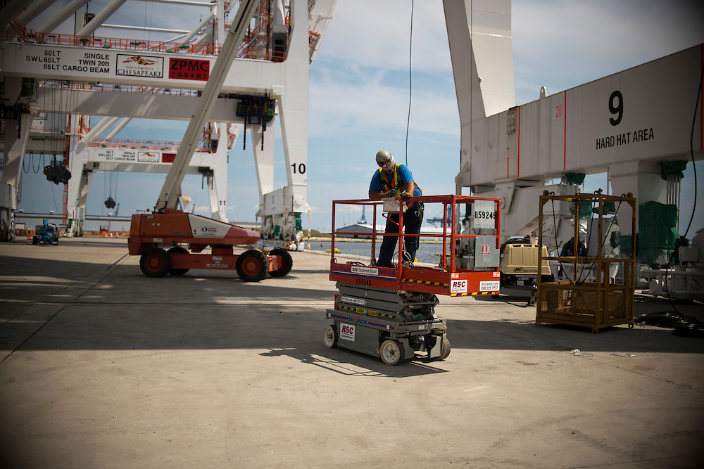 (photo by Matt Roth).Wednesday, July 11, 2012.Assignment ID: 30128574A..Matt Kardczyk, an iron worker from Baltimore local 16, drives a cherry picker under one of the four super-post Panamax cranes -- the largest model built -- during the erection process at The Port of Baltimore's Seagirt Marine Terminal Wednesday, July 11, 2012. ..Once the building, testing and training is finished, the Seagirt terminal will join Norfolk, VA as one of the only two ports on the East Coast which can unload new Panamax sized container ships. The cranes are expected to be fully operational in September of this year.