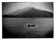Kashmiri woman paddles through a cloudburst, Dal Lake, Srinagar, Indian Administered Kashmir.