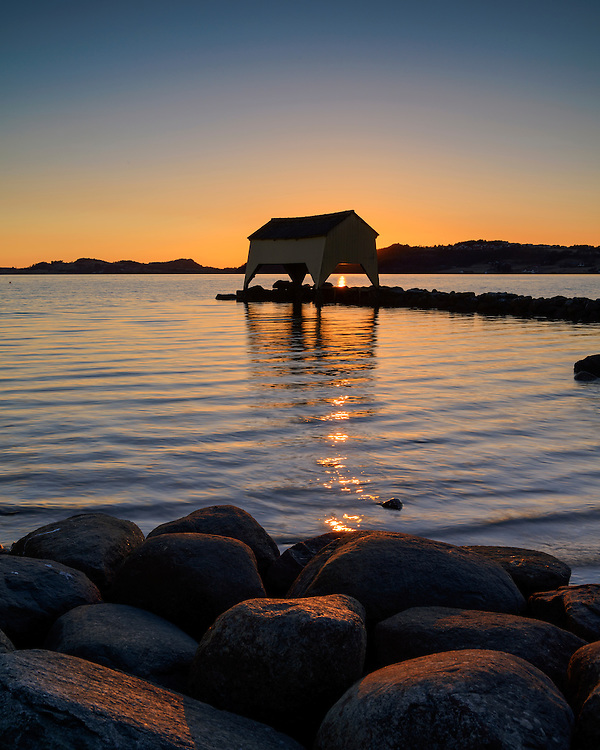 Sunset with the iconic boathouse by the shore of Hafrsfjord, Rogaland, Norway.