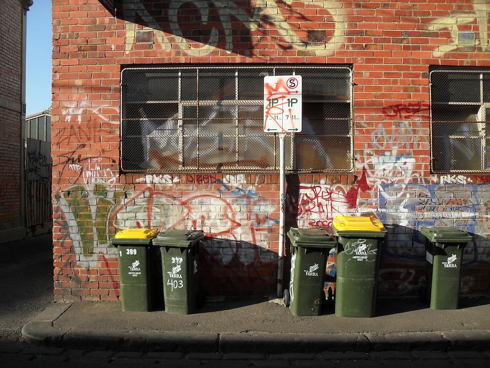 Urban scene with wheelie bins and graffiti
