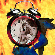 Composite image of vintage couple the man, a winged angel in front of a clock just before midnight on a background of fire. Love, passion, time, heat, rescue, time, youth, anticipation