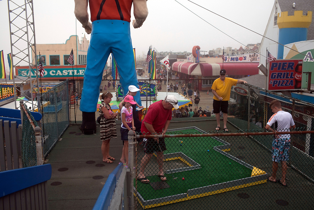 Seaside Heights, NJ - June 30, 2013 : People play mini-golf above the newly restored boardwalk near the Casino Pier that was partially destroyed by Superstorm Sandy at Seaside Heights, NJ on June 30, 2013. People are returning to the beaches for the summer after recovery efforts post Superstorm Sandy.