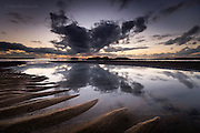 Dramatic evening sky reflecting in a wide sand pool left at low tide, at Broad Beach, Rhosneigr, Anglesey