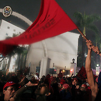 A supporter of Venezuelan President Hugo Chavez waves a flag of the political party Movimiento Quinta Republica in front of Miraflores following news that Chavez was re-elected as president Sunday, December 3, 2006.
